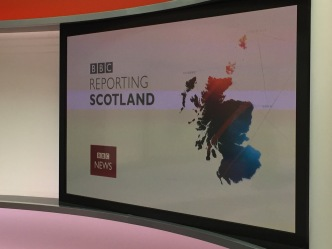 "Screen in the news studio that says, ""BBC Reporting Scotland."""